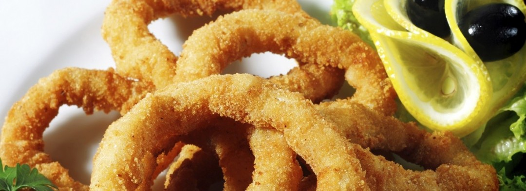 Seafood - Fried Calamari. Deep-fried Squid Dressed with Salad Leaves, Parsley, Olives and Lemon