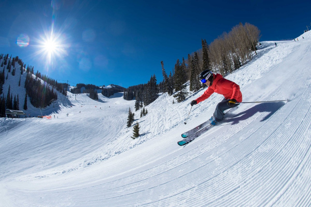 Darcy Conover skiing fresh corduroy down a steep snow covered groomed slope in the mountains at Aspen Mountain Ski Resort in Colorado
