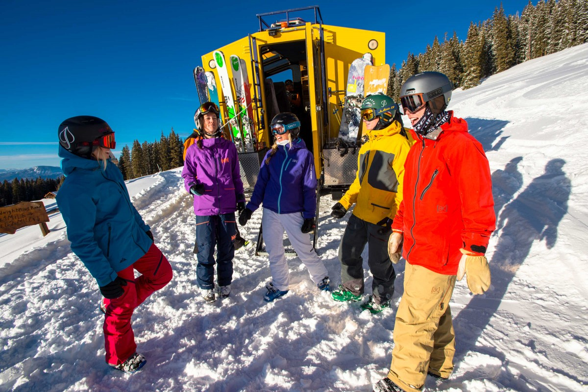 Snowboarders Chris Klug, Robert Pettit and Jordie Karlinski and skiers Gordon Bronson, Chris Davenport, TJ David, Darcy Conover, Lindsy Fortier, Jenny Harris and Julia Hedman standing outside a snowcat in their snowboard and ski gear while getting ready to go skiing in the mountains at Aspen Mountain Ski Resort in Colorado