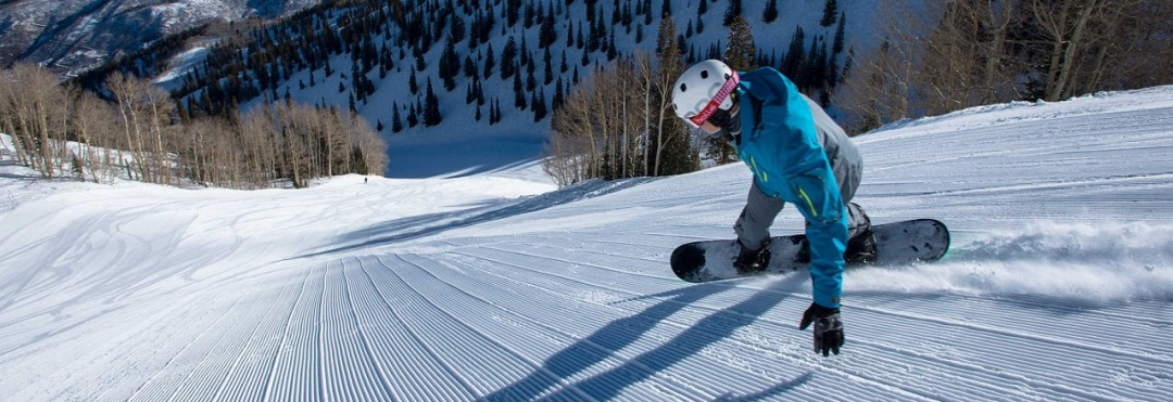 Chris Klug snowboarding down fresh corduroy on a steep snow covered groomed slope in the mountains at Aspen Mountain Ski Resort in Colorado